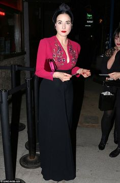 Vintage chic: Dita Von Teese stunned in a plunging cerise blouse as she attended a gig on Thursday