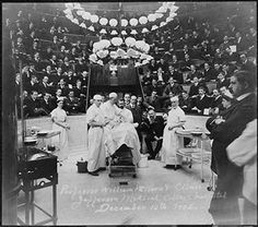 Surgeons gather around the operating table in the clinic amphitheater at the Jefferson Medical College Hospital, with spectators and medical students seated in the background, 1902.