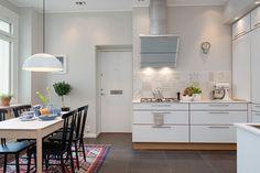 Wzorzysty etniczny dywan umownie wydziela w przestrzeni kuchni strefę jadalnianą. Eklektycznie zestawiono go z nowoczesnym drewnianym stołem i krzesłami w skandynawskim stylu. Urozmaiceniem dla białej nowoczesnej zabudowy jest patchwork wzorzystych kafli nad blatem.