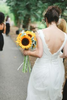 A fashionable shot of the bride and her sunflower bouquet by Boulder Blooms.