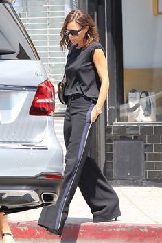 Victoria Beckham in Victoria Beckham top, sunglasses, and bag, Rolex watch, and Victoria Victoria Beckham trousers.