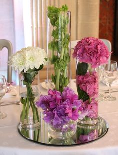 Cylinder cluster centerpieces on a mirror ... Bells of Ireland, hydrangeas, sweet peas and mums.