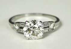 Art Deco Platinum Ring with a 1.70 carat old European cut diamond, flanked by baguette and round diamonds. From greenhilljewelers on Etsy.