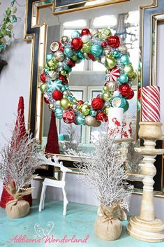A Holiday accent table vignette adds a fun pop of color to a living room wall. A bright ornament wreath and Christmas accessories creates the wow factor!