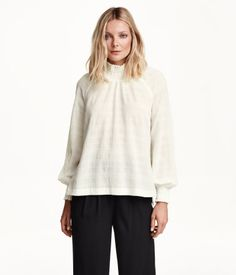 Cotton blouse in a textured weave with long raglan sleeves, a smocked collar with an opening and buttons at the back of the neck, smocking at the cuffs, slits in the sides and a slightly longer back section