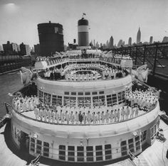 1955: Officers and crew assemble aboard the SS Constitution docked in Manhattan.  The SS Constitution was a passenger ship owned by American Export Lines. She was commissioned in 1951. She sailed on the New York-Genoa-Naples and Gibraltar route to Europe. The Constitution was a sister ship to the SS Independence.  The ships were two of the world's most famous, popular, and innovative ocean liners, following World War 2.