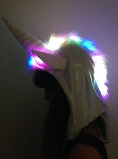 As if being a iridescent unicorn wasnt magical enough, this hood lights up as well! Multicoloured LED fairy lights are securely sewn into the fluffy mane, with a little pocket in the mane for the battery pack (and a popper to keep it safe). Awesome for raves, parties, festivals, fancy dress, anywhere you want to stand out of the crowd! The sparkly fabric of the hood is lined with soft white fleece. The mane, and pompoms (which can be used to tie the hood shut) are made from fluffy, long…