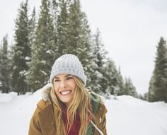 Caucasian woman smiling in snowy forest by Gable Denims