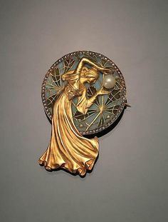 Spanish Art Nouveau Tested 18-Karat Yellow-Gold, Diamond, Cultured Pearl and Plique-a-Jour Brooch, Masriera Hs. (Hermanos), Circa 1900. Modeled as an elegant young woman holding a cultured pearl measuring 6 mm before a plique-à-jour circular disc with leafy branches in shades of green, blue and yellow against a pale-blue ground within a rose-cut diamond border.