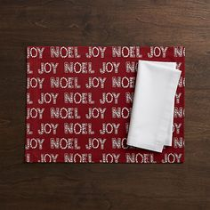 "Designer Kelly Ventura's cheerful design brings tidings of ""joy"" and ""noel"" printed in white letters on a bright red cotton placemat."