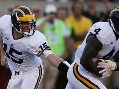 Michigan's quarterback James Ross hands off to De'Veon