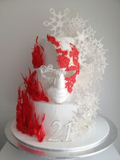 Birthday Cakes - Fire and Ice themed cake.  The flames are isomalt and the snowflakes are gumpaste and isomalt. The mask is gum paste as well . I covered the tiers with sanding sugar to give it that icy look and poured clear isomalt on edges as well.