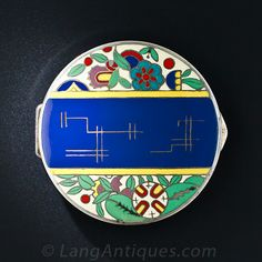 A colorful and artsy round container, circa 1920s, perhaps formerly a compact, adorned on top with a splendid Art Deco floral design rendered in blue, green, yellow, red, lavender and ivory enamel. The reverse shimmers with a radiating engine engraved design. Sterling silver, 2 3/8 inches by just shy of 1/2 inch.