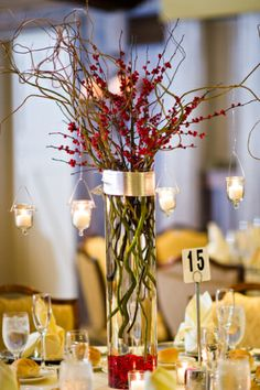 6 Original Wedding Centerpieces  For a beautiful winter wedding centerpiece, hang tea light candles from branches wrapped with holly berries. Guests will be in awe of the soft winter glow