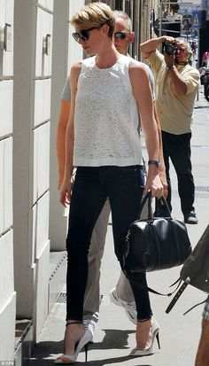 Star attraction: Charlize Theron attracts plenty of attention as she goes shopping in Rome