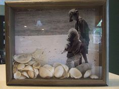 A shadowbox frame with tiny shells from the beach against a black and white seaside photograph. I need a beach.