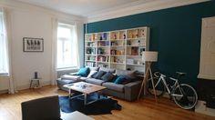 Geräumiges Wohnzimmer mit tiefblauer Wand und großem Bücherregal sowie gemütlicher Couch-Landschaft.  Wohnung in Hamburg.