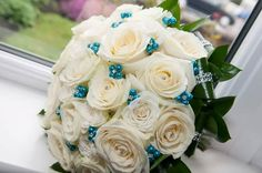 A stunning bridal bouquet of white avalanche roses, and a ruscus foliage collar, tied. With added diamante folded leaves and Teal pearls and diamante pins to accessorise to match the colour theme.