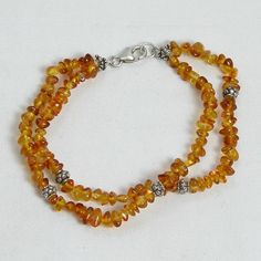 "Handmade gemstone amber bracelet features 2 strands of small, semi-precious honey amber gemstone chips, sterling silver accent beads, lobster claw clasp, and stretch band. 7 1/2"" in length. Add a neck"