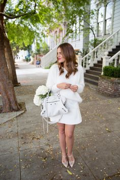 all white fuzzy sweater over a clean-lined dress {via gal meets glam}