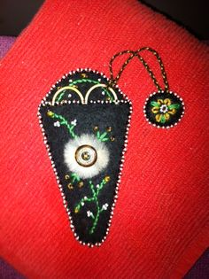 scissors case. Beads, embroidery, coyote fur, button on black felt. Made by Rose Berens. Bois Forte Band of Ojibwe.