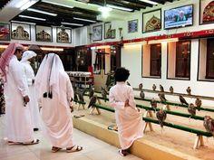 Men and a boy falcon shopping in the Souk Waqif : Photos: It's Falconry Season in Qatar : Condé Nast Traveler