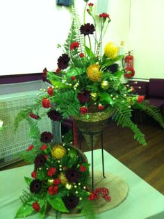 FLOWER ARRANGEMENT: Pin Cushion Protea, 'Black Night' Gerbera, red spray Carnation, Fern, Aucuba, Ivy and Leather Leaf with festive baubles and spray decorations. THEME: Christmas is Coming. BY: Graham Harmer on 20/11/13
