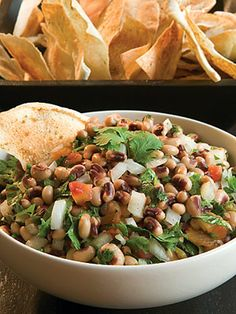 In a large bowl, combine black-eyed peas, tomatoes and green chiles, onion, jalapeno pepper, garlic, cilantro, salt, and pepper. Toss gently with olive oil. Serve with pita chips.