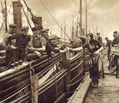This photo appeared in the October 29, 1932 edition of The Sphere.  A Scottish fisher lassie from Buckie who has migrated to Great Yarmouth for the herring harvest, shares a biscuit with the crew of the Cornstalk.