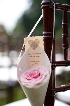 "Single rose petal cone with sign that reads, ""When the newlyweds walk your way toss the petals"""