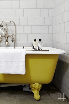We love this! A freestanding bath tub in a gorgeous canary yellow shade, subway tiles and of course, some uplifting Cowshed Grumpy Cow shower gel | Babington House