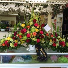 Lime green spider mums, gladiolus, mini green hydrangeas, yellow roses, solidago, red & orange roses & hot pink carnations funeral arrangements by Donna Jeffries & Cyndy Smith