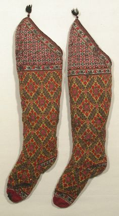 N.D. (probably 19 c.) Pair of knitted wool socks. Persia. The toe is claret, the main part is lemon yellow ground with blue/black/shades of red. The knee has a cream ground with black/reds/green. They are lined with knitted wool. There is a narrow edging of interwoven silk in pink and black with silk cored silver thread with a black tassle. Similar to a pair in Indianapolis Museum of Art 16.1117 aandb. (male) | National Trust Collections