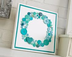 """Button and heart canvas.Here's how to make it.    Gather These Supplies  -------  10"""" x 10"""" blank canvas--  FolkArt acrylic paint - Titanium White, Turquoise---  FolkArt Extreme Glitter - Aqua------  Mod Podge Matte----  Buttons - lots of them in the colors of your choice----  Wood heart piece---  Craft glue----  Stencil tape----  Paintbrush and/or foam spouncer----  Ruler----  Pencil  Craft knife"""