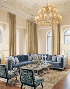 Elegant living room, amazing moldings of course, simple dramatic chandelier and custom blue velvet sofa, fun print in blue on chrs