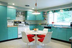 Azulejos cobrem as paredes acima dos armários, que aparecem em abundância e em turquesa neste espaço. No centro, mesa e cadeiras em branco com almofadas vermelhas.