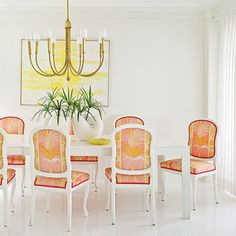 a clean simple room with vibrant dining chairs. love the chandelier.