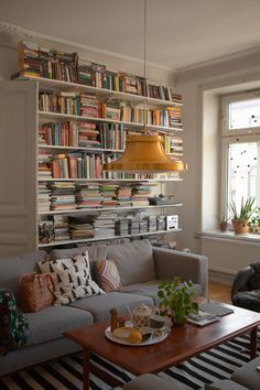 Bookshelf and grey sofa, teak table and brass pendant lamp | Fine Little Day | Photo Elisabeth Dunker