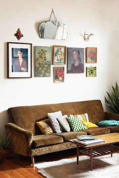 jessica tremp's collection of old portrait paintings and vintage sofa, via dwellstudio.