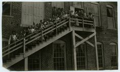 Mill workers, including children, line up on the stairs of a White Oak mill building, circa 1900.