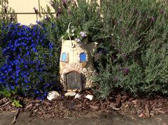 A fairy house made from an old coffee pot.
