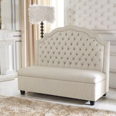 Add a modern Victorian touch to your home decor with the designer Madelyn banquette bench. This gorgeous high back bench is upholstered in button-tufted beige linen and features decorative nail head accents for an elegant touch.
