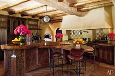 "In keeping with the rest of their Los Angeles–area home's eclectic design scheme, Will and Jada Pinkett Smith's kitchen features reclaimed ceiling beams, cabinetry fashioned from 19th-century Nuristani oak panels, and adobelike walls. As Will Smith told AD, ""Everything needed to be done by hand."" Photo Roger Davies  Please visit Luxury Homes of Las Vegas and Henderson NV at Shirleybrass.com"