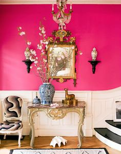 "heeellooo. bright pink, black, white, and gold accessories. ""The entry of a late-19th-century house in Brooklyn is a showstopper, with walls in Benjamin Moore's Razzle Dazzle. The table and side chair — covered in vintage needlepoint — are Louis XV, and the mirror is 18th-century Italian."""