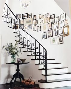 """""""Family photo walls can look great -- or totally cheesy,"""" Turner writes in a caption for this photo of Peet's stairwell. """"For me the key is to mix it up so you're including old pictures, new pictures, solo shots, group shots."""" The key to this wall, he adds, was a mix of frames in different finishes to reference the mix of styles in the house. Before you get the hammer and hooks, the designer advises, """"lay the arrangement out on the floor and create your grouping or use craft paper cutouts…"""