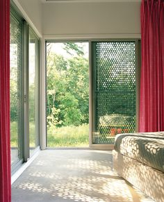 In the master bedroom, the same perforated material that was used in the bathroom gives a sense of sunlight filtering through leaves.