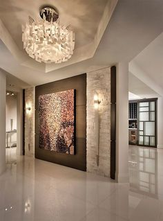 exquisite strong entry.... large wall light fixtures, large painting, glamorous chandelier, rock wall