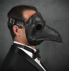 This mask is our classic Plague Doctor mask, but with metal rivets rather than hand stitching, which gives it a bit of a steampunk look. The eyepieces are sewn in with waxed thread. The mask is painted black and the lenses are gray acrylic.