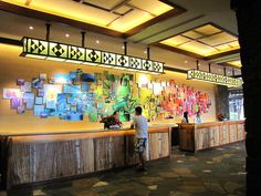 I like the idea of a montage of images with a gradient of colors.  Perhaps it could go around the whiteboard?  The whiteboard/wall area could use sprucing up.   ~Natalie  Aulani front desk by LauraSBly, via Flickr