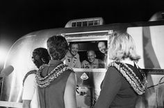 Apollo 11 astronauts, still in their quarantine Airstream, are greeted by their wives upon arrival at Ellington Air Force Base.